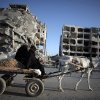 Photo - Two Palestinian women ride a donkey cart past the destroyed Nada Towers residential neighborhood in the town of Beit Lahiya, northern Gaza Strip, Monday, Aug. 11, 2014.  A new temporary truce took hold, Monday, in the monthlong war pitting the Israeli military against rocket-firing Hamas militants as negotiators from Israel and the Hamas militant group resumed indirect talks in Egypt on Monday. (AP Photo/Khalil Hamra)