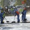 Photo - Crews sop up the remains of about 10,000 gallons of crude oil in the Atwater Village section of Los Angeles on Thursday, May 15, 2014. A geyser of crude spewed 20 feet high over approximately half mile into Los Angeles streets and onto buildings early Thursday after a high-pressure pipe burst. (AP Photo/Nick Ut )
