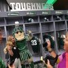 Photo - In this Monday, Aug. 25, 2014, photo, Terri Conway, of Grand Rapids, poses for a photo with Sparty in the new home locker room as her father Greg Conway stands by as her mother Amy Conway takes a photo during a tour of the new North End Zone Complex renovations at Spartan Stadium on the Michigan State Campus in East Lansing, Mich. (AP Photo/Detroit Free Press, Ryan Garza)  DETROIT NEWS OUT, TV OUT, INTERNET OUT, MAGS OUT, NO SALES, MANDATORY CREDIT DETROIT FREE PRESS