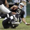 Oakland Raiders quarterback Carson Palmer is sacked by New Orleans Saints defensive tackle Tom Johnson, below, during the third quarter of an NFL football game in Oakland, Calif., Sunday, Nov. 18, 2012. (AP Photo/Marcio Jose Sanchez)