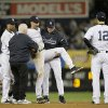 Trainer Steve Donohue, second from left, and New York Yankees manager Joe Girardi, second from right, help Derek Jeter off the field after he injured himself during Game 1 of the American League championship series against the Detroit Tigers Sunday, Oct. 14, 2012, in New York. New York Yankees\' Robinson Cano, left, and Eric Chavez stood by. (AP Photo/Matt Slocum)