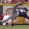 Photo - Cincinnati Reds' Brandon Phillips, left, slides hard into Milwaukee Brewers shortstop Jean Segura (9) to break up a double play after being forced out at second base in the first inning of a baseball game on Sunday, July 6, 2014, in Cincinnati. Reds' Jay Bruce was safe at first and Todd Frazier scored on the play. (AP Photo/Al Behrman)