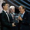 Photo - UEFA President Michel Platini, right, gives the trophy for best player of the year to Real Madrid Portuguese forward Cristiano Ronaldo, during the UEFA Champions League draw, at the Grimaldi Forum, in Monaco, Thursday, Aug. 28, 2014. (AP Photo/Claude Paris)