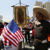 An immigrant wearing a traditional charro hat from Mexico, right, holds a banner of Mexico\'s Virgin of Guadalupe, as they gather to march during a May Day rally in downtown Los Angeles on Wednesday, May 1, 2013. In celebration of May Day, people have gathered across the country to rally for various topics including immigration reform. (AP Photo/Damian Dovarganes)