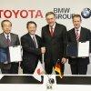 Photo - In this photo released by Toyota Motor Corp., Toyota President Akio Toyoda, third left, shakes hands with BMW AG chief executive Norbert Reithofer, third right, as their executives show signed documents during a signing ceremony to jointly develop next-generation batteries for green vehicles in Nagoya, central Japan, Thursday, Jan. 24, 2013.  Toyota and BMW are working together on next-generation batteries for green vehicles called