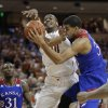 Photo - Texas' Jonathan Holmes (10) and Kansas' Landen Lucas, right, scramble for a rebound during the first half of an NCAA college basketball game, Saturday,  Feb. 1, 2014, in Austin, Texas. (AP Photo/Eric Gay)