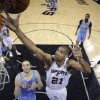 San Antonio Spurs\' Tim Duncan (21) grabs a rebound over Denver Nuggets\' Kosta Koufos (41) during the first half of an NBA basketball game, Wednesday, March 27, 2013, in San Antonio. (AP Photo/Eric Gay)