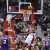 Washington Wizards guard John Wall, center, goes to the basket against Phoenix Suns forward Michael Beasley (0) and Wesley Johnson, left, during the first half of an NBA basketball game on Saturday, March 16, 2013, in Washington. (AP Photo/Nick Wass)