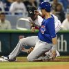 Photo - After tagging up from second  base, Chicago Cubs' Chris Coghlan (8) slides into third as Miami Marlins's third baseman Casey McGehee fields the late throw during the first inning of a baseball game in Miami, Wednesday, June 18, 2014.  (AP Photo/J Pat Carter)