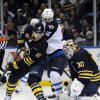 Buffalo Sabres\' defenseman Christian Ehrhoff (10), of Germany, battles with Winnipeg Jets\' left winger Andrew Ladd (16) as Buffalo goaltender Ryan Miller (30) makes a save during the second period of an NHL hockey game in Buffalo, N.Y., Tuesday, Feb. 19, 2013. (AP Photo/Gary Wiepert)