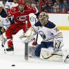 Buffalo Sabres goalie Ryan Miller (30) eyes the puck in front of a charging Carolina Hurricanes\' Tim Wallace (29) and Sabres\' T.J. Brennan (33) during the second period of an NHL hockey game, Tuesday, March 5, 2013, in Raleigh, N.C. (AP Photo/Karl B DeBlaker)