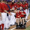 Oklahoma City police officer Chad Peery and sons McKade, 6, left, and Morgan, 4, are greeted by members of the Oklahoma City RedHawks as Peery rolls down the third-base line in his wheelchair while rounding the bases after the third inning as part of the