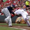 Photo - Cincinnati Reds' Billy Hamilton, right is tagged out at first by Cleveland Indians first baseman Carlos Santana, left, during the first inning of a baseball game, Wednesday, Aug. 6, 2014, in Cincinnati. (AP Photo/David Kohl)