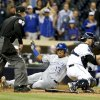 Photo - Kansas City Royals' Salvador Perez beats the throw to San Diego Padres catcher Yasmani Grandal while scoring the go ahead run in the 12th inning of a baseball game Monday, May 5, 2014, in San Diego.  (AP Photo/Lenny Ignelzi)