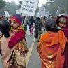 Indian women carry their children as they march during a protest to mourn the death of a gang rape victim in New Delhi, India, Wednesday, Jan. 2, 2013. India\'s top court said it will decide whether to suspend lawmakers facing sexual assault charges as thousands of women gathered at the memorial to independence leader Mohandas K. Gandhi to demand stronger protection for their safety. The writing on the sign in foreground reads