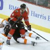 Photo - Philadelphia Flyers left wing Scott Hartnell (19) battles Chicago Blackhawks defenseman Niklas Hjalmarsson (4) for a loose puck during the first period of an NHL hockey game on Wednesday, Dec. 11, 2013, in Chicago. (AP Photo/Charles Rex Arbogast)