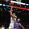 Photo - Brooklyn Nets' Deron Williams (8) shoots a basket over Sacramento Kings Isaiah Thomas (22) in the first half of an NBA basketball game on Sunday, March 9, 2014, at Barclays Center in New York. (AP Photo/Kathy Kmonicek)