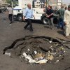 Photo - Civilians inspect a crater caused by a car bomb explosion in commercial area of New Baghdad, Iraq, Tuesday, Aug. 26, 2014. The parked car bomb exploded on Tuesday in a busy area in eastern Baghdad, killing and wounding scores of people, officials said, the latest in a series of attacks to shake the Iraqi capital as the Shiite-led government struggles to dislodge Sunni militants from areas in the country's west and north. (AP Photo/ Khalid Mohammed)
