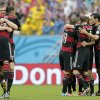 Germany\'s Per Mertesacker, left, hugs his teammate Mesut Ozil after Germany\'s Thomas Mueller scored the opening goal during the group G World Cup soccer match between the USA and Germany at the Arena Pernambuco in Recife, Brazil, Thursday, June 26, 2014. (AP Photo/Matthias Schrader)