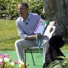 President Barack Obama, accompanied by first dog Bo, reads