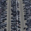 In this Friday, Jan. 18, 2013 aerial photo, a forklift, left, moves a car for storage among the thousands of cars which were damaged in the Oct. 29, 2012 Superstorm Sandy and stored on the runways at Calverton Executive Airpark in Calverton, N.Y. Environmentalists are decrying the placement of the 18,000 damaged automobiles at the defunct defense plant on eastern Long Island near the environmentally protected Pine Barrens. The town supervisor in Riverhead disputes the idea that there is any hazard. The town leased the runways to salvage companies and could reap up to $2.7 million under the lease agreement. (AP Photo/Mark Lennihan)