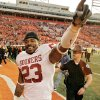 Photo - BEDLAM: Oklahoma's Allen Patrick (23) celebrates with the fans as he walks off the field after the 27-21 win over the Cowboys  during the University of Oklahoma Sooners (OU) college football game against Oklahoma State University Cowboys (OSU) at Boone Pickens Stadium, on Saturday, Nov. 25, 2006, in Stillwater, Okla.     by Chris Landsberger, The Oklahoman  ORG XMIT: KOD