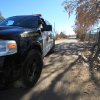 A Bernalillo County sheriff\'s deputy blocks the dirt road that leads to a home where detectives on Sunday, Jan. 20, 2013, were investigating the deaths of five people who were shot to death south of Albuquerque, N.M. Authorities say a teenager has been arrested and booked on murder and other charges in connection with the shootings. (AP Photo/Susan Montoya Bryan)