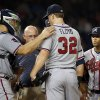 Photo - Atlanta Braves manager Fredi Gonzalez, far left, catcher Evan Gattis, head athletic trainer Jeff Porter look at starting pitcher Gavin Floyd, with shortstop Andrelton Simmons and second baseman Tommy La Stella, during the seventh inning of a baseball game against the Washington Nationals at Nationals Park Thursday, June 19, 2014, in Washington. Floyd left the game. The Braves won 3-0. Atlanta Braves right-hander Gavin Floyd left Thursday night's game against the Washington Nationals with an elbow injury in his ninth start since returning from Tommy John surgery.(AP Photo/Alex Brandon)