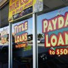 Photo -  Windows advertising payday loans are seen at Approved Cash, 3623 NW 39 Street, in Oklahoma City.    PAUL B. SOUTHERLAND