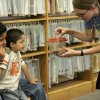 Erik Guijarro, 12, and his brother Ivan Guijarro, 4, inspect the scorpion being held by Angela Hilliard, from the education department of the Science Museum Oklahoma, at the Capitol Hill public library on Thursday, June 5, 2008. By Amy Rymer, The Oklahoman