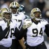 New Orleans Saints\' Akiem Hicks (76) and Cameron Jordan (94) celebrate after tackling Philadelphia Eagles\' Nick Foles during the second half of an NFL wild-card playoff football game, Saturday, Jan. 4, 2014, in Philadelphia. (AP Photo/Michael Perez)