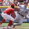 Photo - Cincinnati Reds second baseman Brandon Phillips (4) tags out Colorado Rockies' Corey Dickerson (6) trying to steal second base in the fourth inning of a baseball game, Sunday, May 11, 2014, in Cincinnati. (AP Photo/Al Behrman)