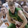 Oklahoma State guard Phil Forte, left, reaches for the ball in between the arms of Oregon forward E.J. Singler during the first half of a second-round game in the NCAA college basketball tournament in San Jose, Calif., Thursday, March 21, 2013. (AP Photo/Jeff Chiu) ORG XMIT: SJA120