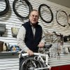 Hank Ryan, co-owner of Al's Bicycles, holds a folded Brompton bicycle. Photo by STEVE SISNEY, THE OKLAHOMAN