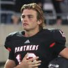 Photo - Colleyville Heritage senior quarterback Cody Thomas (12) during the playing of the national anthem before the start of his team's game against Flower Mound at Pennington Field on Friday, September 14, 2012. (Kelley Chinn/Special Contributor)