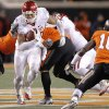 Oklahoma\'s Trey Millard (33) runs through the Oklahoma State defense during the Bedlam college football game between the Oklahoma State University Cowboys (OSU) and the University of Oklahoma Sooners (OU) at Boone Pickens Stadium in Stillwater, Okla., Saturday, Dec. 3, 2011. Photo by Chris Landsberger, The Oklahoman
