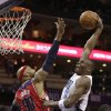 Charlotte Bobcats\' Bismack Biyombo (0) goes up to dunk over Washington Wizards\' Drew Gooden (90) during the first half of an NBA basketball game in Charlotte, N.C., Monday, March 31, 2014. (AP Photo/Chuck Burton)