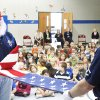 Photo - Terry Farmer and Harmon Thompson, members of the Oklahoma Veterans Flag Program, demonstrate the proper way to fold an American flag.