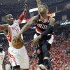 Photo - Portland Trail Blazers' Damian Lillard, right, looks to pass the ball around Houston Rockets' Dwight Howard (12) in the first half of Game 5 of an opening-round NBA basketball playoff series Wednesday, April 30, 2014, in Houston. (AP Photo/Pat Sullivan)