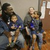 Photo - In this Tuesday, April 8, 2014 photo Anthony Johnson, left, his wife Candice with their children Zayden,1 and Anthony Jr., 4, in Kissimmee, Fla. wait at the Community Hope Center to see if they qualify for aid to find an apartment of their own. (AP Photo/John Raoux)