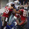 Tampa Bay Buccaneers\' D.J. Ware (28) and Vincent Jackson (83) attempt to bring down Dallas Cowboys inside linebacker Sean Lee (50) after Lee intercepted a pass in the first quarter of an NFL football game, Sunday, Sept. 23, 2012, in Arlington, Texas. (AP Photo/Tony Gutierrez)
