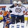 Photo - Winnipeg Jets' Blake Wheeler (26) and Andrew Ladd (16) celebrate a goal as Edmonton Oilers' Corey Potter (44) skates past during the second period of an NHL hockey game in Edmonton, Alberta, on Monday, Dec. 23, 2013. (AP Photo/The Canadian Press, Jason Franson)