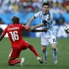 Photo - Argentina's Marcos Rojo tries to stop Argentina's Lionel Messi during the World Cup round of 16 soccer match between Argentina and Switzerland at the Itaquerao Stadium in Sao Paulo, Brazil, Tuesday, July 1, 2014. (AP Photo/Victor R. Caivano)