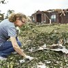 Above and right: Donna Hensley gathers personal belongings scattered in the debris Wednesday. Hensleys home was destroyed by a tornado Monday.