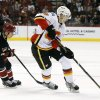 Calgary Flames\' Joe Colborne (8) skates with the puck in front of Phoenix Coyotes\' David Moss (18) during the first period of an NHL hockey game, Tuesday, Jan. 7, 2014, in Glendale, Ariz. (AP Photo/Ross D. Franklin)