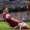 Photo -   Arsenal's Laurent Koscielny, center, celebrates scoring against Manchester City with teammate Santi Cazorla during their English Premier League soccer match at The Etihad Stadium, Manchester, England, Sunday, Sept. 23, 2012. (AP Photo/Jon Super)