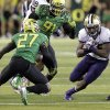 Washington running back Bishop Sankey, right, looks to gain yardage against Oregon defenders Terrence Mitchell, left, and Dane Ebanez during the first half of an NCAA college football game in Eugene, Ore., Saturday, Oct. 6, 2012. (AP Photo/Don Ryan)