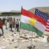 Photo - U.S. and Kurdish flags flutter in the wind while displaced Iraqis from the Yazidi community cross the Syria-Iraq border at Feeshkhabour bridge over the Tigris River at Feeshkhabour border point, in northern Iraq, Sunday, Aug. 10, 2014. Kurdish authorities at the border believe some 45,000 Yazidis passed the river crossing in the past week and  thousands more are still stranded in the mountains. (AP Photo/ Khalid Mohammed)
