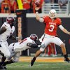 OSU quarterback Brandon Weeden (3) passes the ball as he is pursued by Troy\'s Jonathan Massaquoi (94) and Mario Addison (7) in the first quarter during the college football game between the Oklahoma State University Cowboys (OSU) and the Troy University Trojans at Boone Pickens Stadium in Stillwater, Okla., Saturday, Sept. 11, 2010. Photo by Nate Billings, The Oklahoman