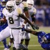 Photo - Baylor Bears running back Glasco Martin (8) runs past Kansas Jayhawks safety Isaiah Johnson (5) for a touchdown run in the first quarter of an NCAA college football game Saturday, Oct. 26, 2013, in Lawrence, Kan. (AP Photo/Ed Zurga)